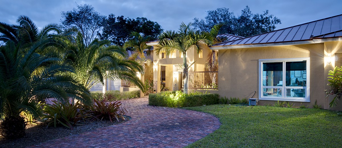 Exterior of a Florida home at dusk with exterior lighting purchased after home buyer's inspection services.
